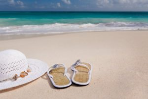 Image of white hat and sandals on a beach