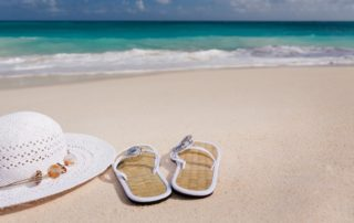 Image of white hat and sandals on a trash-free beach